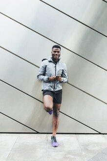 Portrait of smiling athlete leaning against building front - BOYF00679