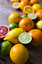 Sliced and whole limes, oranges and lemons on wood - GIOF02237
