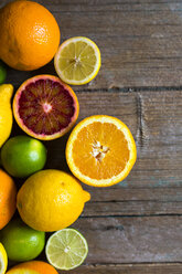 Sliced and whole lemons, oranges and limes on wood - GIOF02240
