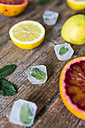 Sliced and whole lemons and oranges, mint leaves and ice cubes on wood - GIOF02243