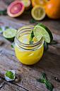 Glass of orange juice, limes, lemon and ice cubes - GIOF02246