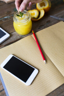 Glass of orange juice, notepad, pencil and cell phone - GIOF02252