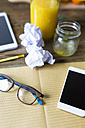 Glass bottle of orange juice, empty glass, notepad, spectacles, tablet, cell phone and crumpled paper - GIOF02255