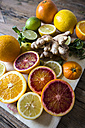 Sliced and whole lemons, oranges and limes, ginger root and mint leaves on wooden board - GIOF02264