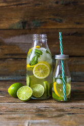 Glass bottles of infused water with lemon, lime, mint leaves and ice cubes - GIOF02267