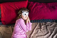 Girl with sleep mask lying on bed - XCF00144