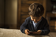 Toddler playing with smartphone at home - JASF01571