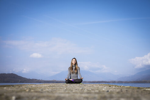 Woman practicing yoga on a pier at a lake - SIPF01464