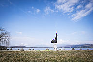 Woman practicing yoga doing a headstand at a lake - SIPF01470