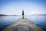 Woman practicing yoga doing a headstand on a pier at a lake - SIPF01473