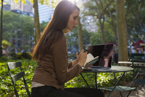 USA, New York, Manhattan, young businesswoman with laptop and notebook sitting at table in a park - BOYF00693