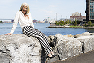 USA, Brooklyn, smiling mature woman sitting on a wall - GIOF02282
