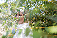 Portrait of smiling woman behind twigs - GIOF02285