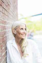 Portrait of smiling mature woman wearing white shirt blouse leaning against brick wall - GIOF02291