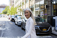 USA, Brooklyn, portrait of smiling mature woman crossing the street - GIOF02297