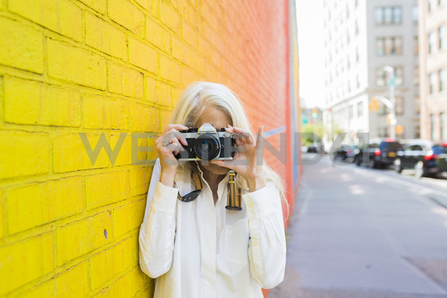 Mature woman leaning against wall taking picture with camera - GIOF02300 - Giorgio Fochesato/Westend61