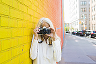 Mature woman leaning against wall taking picture with camera - GIOF02300