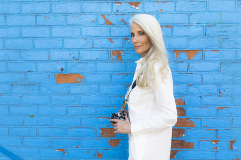 Portrait of mature woman with camera in front of blue wall - GIOF02303