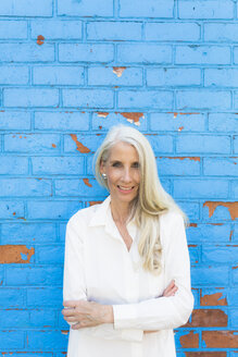 Portrait of smiling mature woman in front of light blue wall - GIOF02306