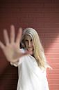 Portrait of mature woman raising her hand - GIOF02312