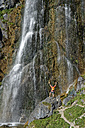 Austria, Tyrol, Rofan Mountains, hiker at Dalfaz waterfall - LBF01596