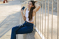 Portrait of smiling young woman with smartphone sitting on a wall - GIOF02325