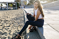Portrait of young woman sitting on beach promenade at sunset - GIOF02328