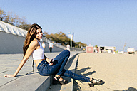 Smiling young woman relaxing on beach promenade at sunset - GIOF02331
