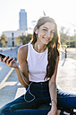 Spain, Barcelona, portrait of smiling young woman relaxing at sunset listening music with earphones - GIOF02337