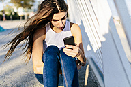 Young woman looking at cell phone at sunset - GIOF02343
