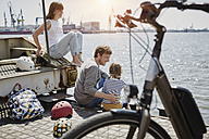 Germany, Hamburg, family having a break from a bicycle tour at River Elbe - RORF00682