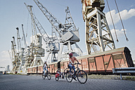 Germany, Hamburg, family riding e-bikes at the harbor - RORF00700