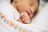 Newborn baby girl sleeping under blanket with floral pattern - GEMF01528
