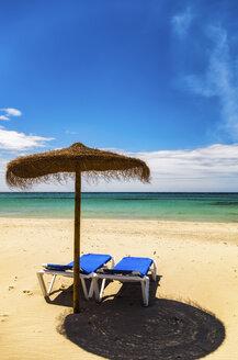 Spain, Menorca, Son Bou, beach with sunshade and sun loungers - SMAF00710