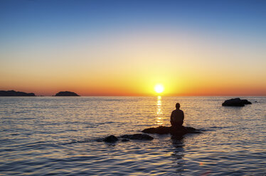 Spain, Menorca, Playa de Cavalleria, man on rock in the sea at sunset - SMAF00725
