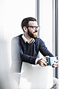 Young businessman sitting on chair drinking coffee - UUF10146