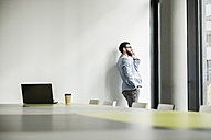 Young businessman standing in office, using smart phone - UUF10149
