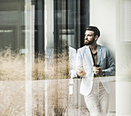 Young businessman standing in office, using smart phone - UUF10155