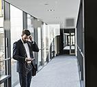 Businessman with earphones talking on smart phone in office building - UUF10170