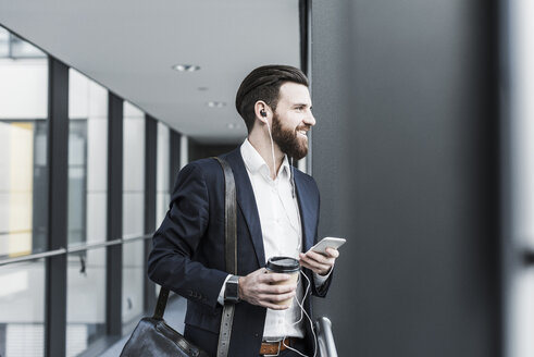 Businessman walking in office building while talking on the phone with ear phones - UUF10173
