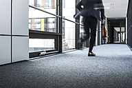 Businessman running in corridor of an office building - UUF10176