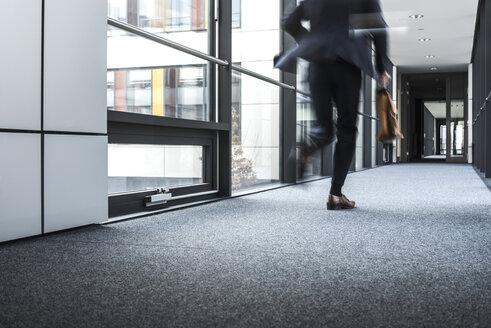 Businessman running in corridor of an office building - UUF10176
