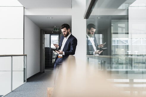 Businessman standing in office building, using smart phone and digital tablet - UUF10182