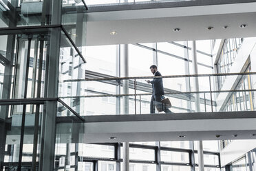 Businessman walking in office building, while using smart phone - UUF10185