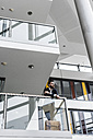 Businessman standing in office building, thinking - UUF10188