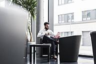 Businessman sitting in lobby, drinking coffee, reading documents - UUF10197