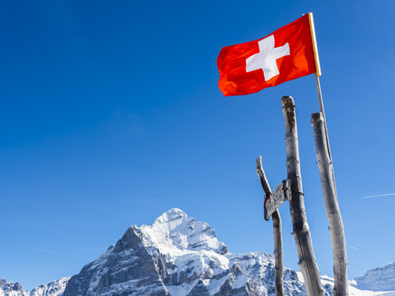 Switzerland, Canton of Bern, Grindelwald, Swiss flag in the mountains - AMF05354