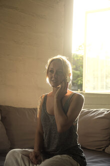 Blond woman on the phone sitting on the couch at backlight - KNTF00814