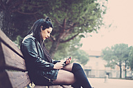 Dark-haired young woman sitting on bench listening music with earphones and smartphone - SIPF01484