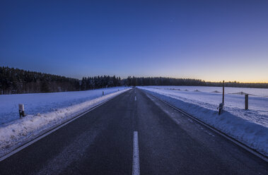 Germany, Saxony-Anhalt, Tanne, road at winter evening - PVCF01037